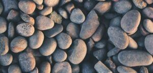 River pebbles. Image by Aaron Burden via unsplash.com.