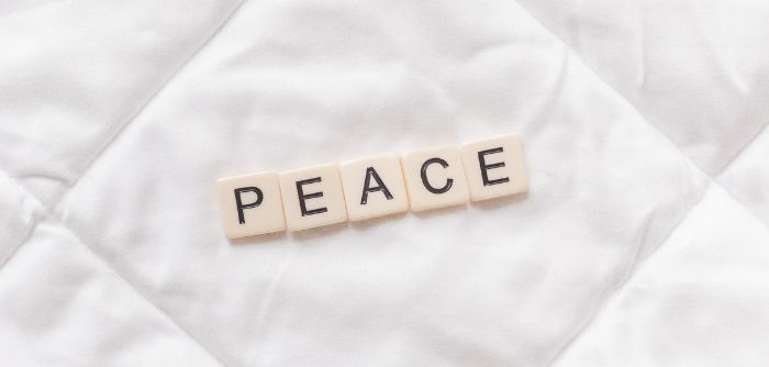A weighted blanket with the word peace. Photo by Sincerely Media via unsplash.com.