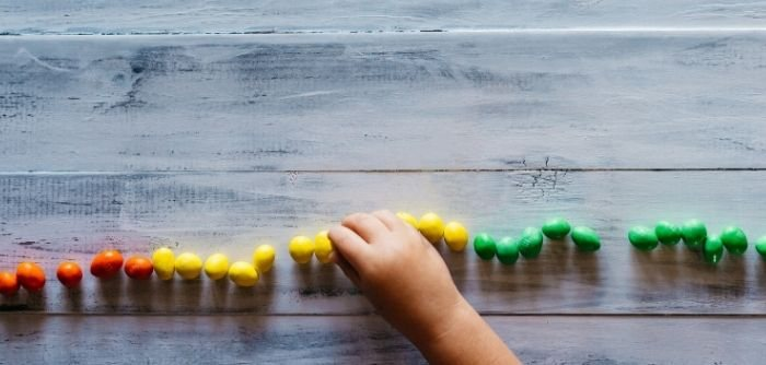 A photo of a child's hand sorting beads to suggest someone with Asperger's Syndrome. Photo courtesy of unsplash.com.