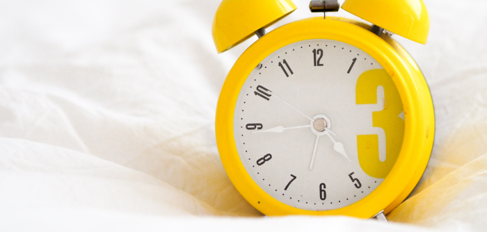 A yellow alarm clock on a bed. Photo by Laura Chouette via unsplash.com.